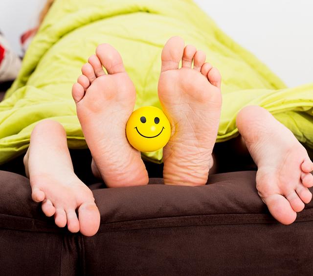 Pie de las personas sosteniendo un emoticomo sonrindo
